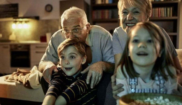 Older couple watching TV with children